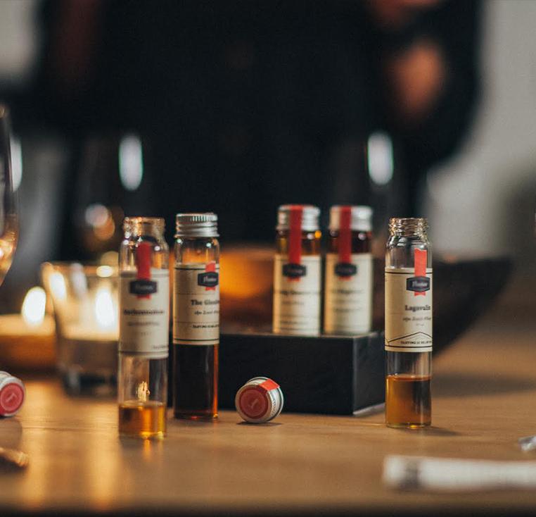 photo de mignonnette de dégustation de rhum au centre de l'image posé sur une table en bois