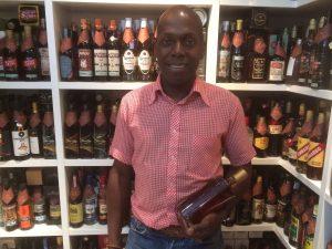 Photo de Freddy au centre, en chemise rose tenant une bouteille de rhum à la main avec en arrière plan les étales de bouteille de la boutique de À'Rhûm